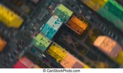 Dynamic rapid fall from high altitude to colored residential buildings, POV. Free fall effect with clockwise rotation background. Fall down at high speed. Dynamic rapid fall. Top view.