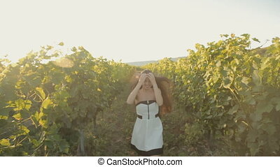 Free girl in the dress runs along the vineyard