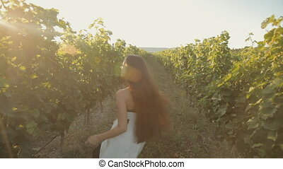 Free girl in the dress runs along the vineyard