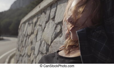 Free girl leaned against the stone wall and then walking on the road