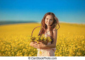 Free happy young woman in rape field enjoying life. Pretty brunette with long healthy hair. Carefree girl over yellow field and blue sky. Countryside landscape Lifestyle.