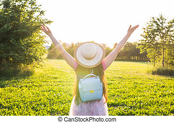 Free happy young woman raising arms watching the sun in the background at sunrise