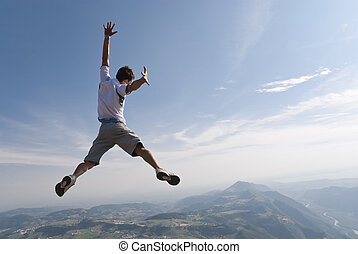 Free man - back shot - Healthy young man jumping in mid-air...
