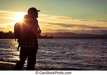 free silhouette man standing near the lake