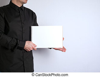 Free space for text, marketing education and business information. Man with a notebook on white background