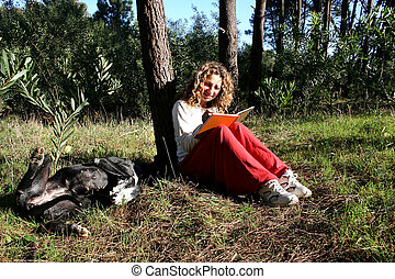 Digital photo of a woman writing her diary outside.