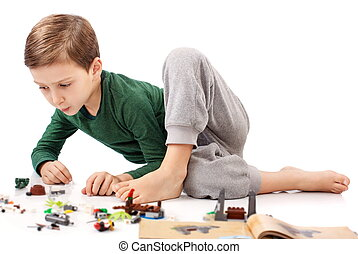 Handsome guy who is playing and building something from book