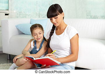 Portrait of cute girl and her mother having rest at home