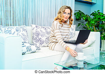 free time - Smiling elegant woman sitting on a sofa with her...
