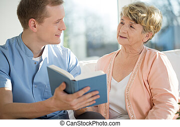 Young male nurse spending his free time with elderly woman