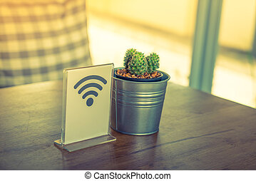 Free Wifi sign on table ( Filtered image processed vintage...