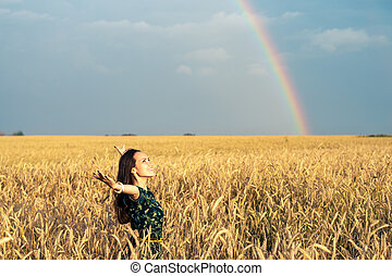 Free woman in a field with Golden wheat ears with her hands open watching the sunset on a rainbow background