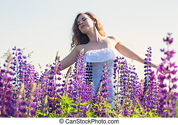 Free woman in the field of lupines