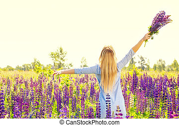 Free woman with bouquet on the field