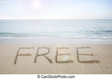 Free word handwritten in sand on sunny beach with sun sky...