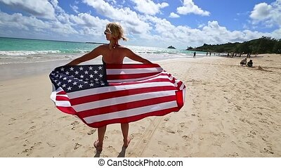 backside of Hawaiian woman holding a waving American flag wearing in American flagged bikini. Tropical Lanikai Beach, east shore of Oahu in Hawaii, USA. Freedom and 4th July patriotic concept.