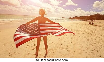 backside of Hawaiian woman holding at sunset an American flag wearing in American flagged bikini. Tropical Lanikai Beach, east shore of Oahu in Hawaii, USA. Freedom and 4th July patriotic concept.
