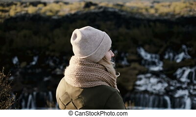 Freedom: back view of young beautiful woman stand near the Barnafoss waterfall in Iceland, jumping and raising up hands.