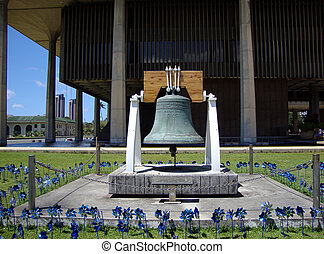 Freedom bell and blue pinwheels in front of the Hawaii State Capitol