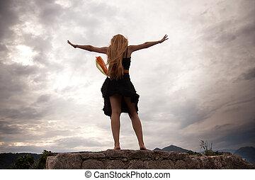 Freedom concept - woman on mountain peak
