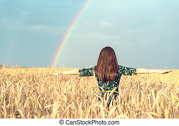 Freedom. Happy smiling woman with open hands in wheat field with Golden spikelets looking up at the sky on rainbow background