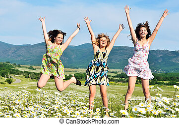 freedom - happy teen girls jumping in daisy field