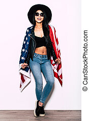Freedom in in her veins. Full length of beautiful young mixed race woman carrying American flag on shoulders and smiling while standing against white background
