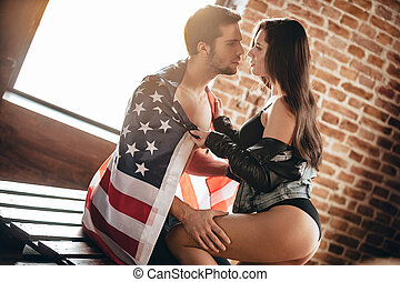 Freedom is in their veins. Side view of beautiful young woman with perfect buttocks adjusting American flag on her boyfriend shoulders and leaning to him while sitting on wood table in loft interior