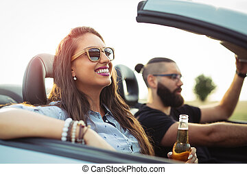 Freedom of the open road.Young Couple Driving Along Country Road In Open Top Car.