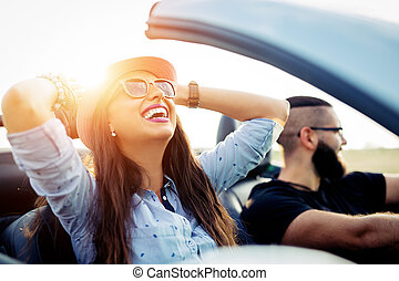 Freedom of the open road.Young Couple Driving Along Country Road In Open Top Car