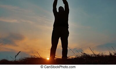 Freedom or success concept silhouette. man silhouette stands on the edge of a precipice nature landscape hands to sides freedom concept religion belief in god