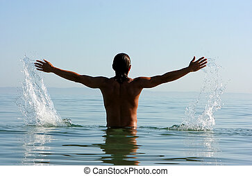 Freedom - Muscular man spreading hands and making splashes...