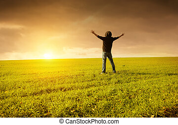 Freedom - Man in a green field raising his hands for happy...