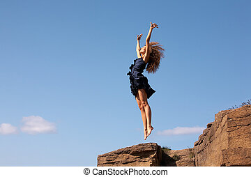 Freedom - Photo of delighted female leaping over rocky cliff...