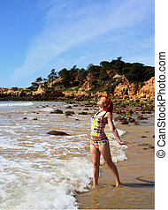 freedom - woman soaks up the sun at the beach in the...