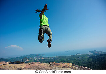 freedom woman jumping on rocky mountain top