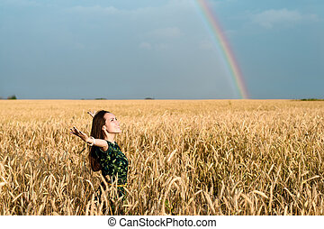 Freedom. Woman with open hands on wheat field on a background of rainbows