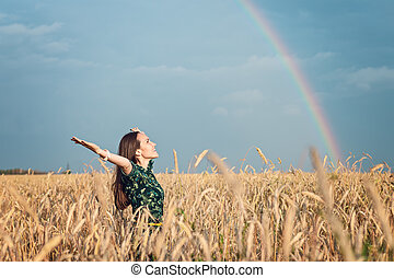Freedom. Woman with open hands smiling looking at the sky against the rainbow