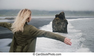 Freedom: young beautiful woman standing on the shore of the black beach, near the sea and looking on the landscape.