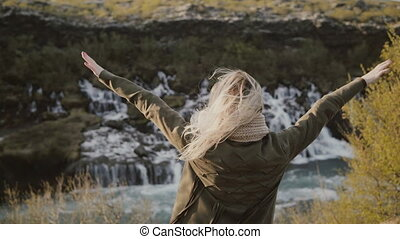 Freedom: young traveling woman looking on waterfalls in Iceland and raising hands up, feeling happy.