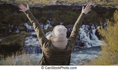 Freedom: young woman standing near waterfalls in Iceland and raising hands up, takes off hat and feeling happy.