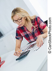 freelance woman calculating a budget in a desktop at office