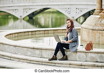 Freelance woman sitting at fountain