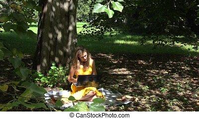 Freelancer beautiful girl working in park. 4K