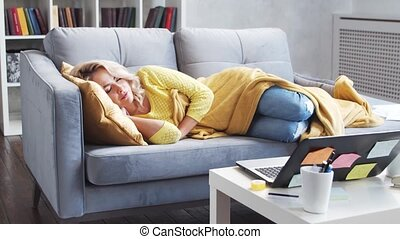 Freelancer girl tired of work sleeps on the couch in the morning. Young woman fell asleep while working at home. Lockdown and remote job concepts.