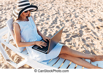 Freelancer girl working on vacation, in front of the beautiful sea, sitting with a laptop on the ocean