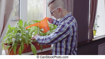 Freelancer man standing by the window watering plants. Male ...