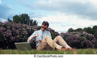 Freelancer talking on video calling with a laptop sitting on grass at city park