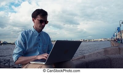 Freelancer using laptop sitting on bench near seafront. Summer day
