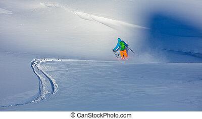 Freerider skier running downhill in fresh powder snow